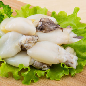 Raw cuttlefish with herbs on the wood background